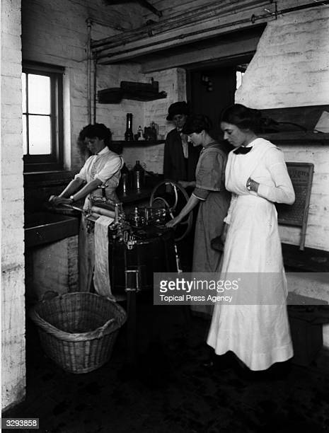 Lady Gwendolen Guinness watches laundry students using a mangle at the Rupert Guinness Training Farm for Women Hoebridge Farm Woking The school is...