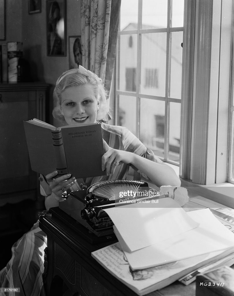 Actress Jean Harlow (1911 - 1937) studies the novel 'Red Headed Woman' witten by Katherine Brush, on which the film of the same name was based. Harlow took the lead role in the film directed by Jack Conway.