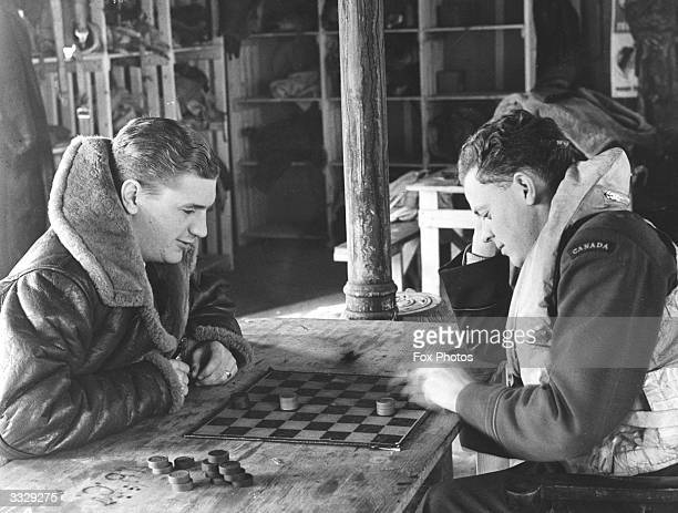 Two Canadian fighter pilots of the Royal Canadian Air Force while away the time with a game of draughts while standing by