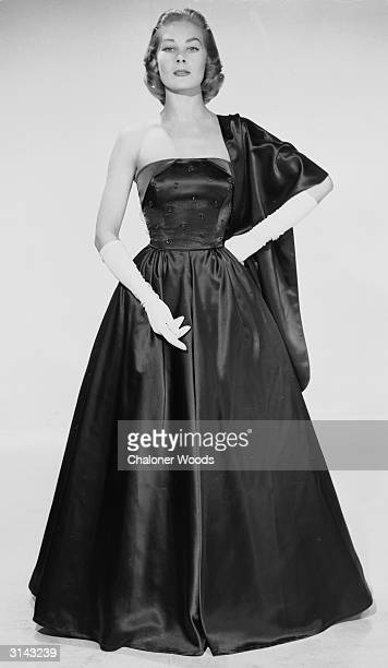 A haughty woman wearing a full length strapless dark satin evening dress with a matching wrap and long white gloves