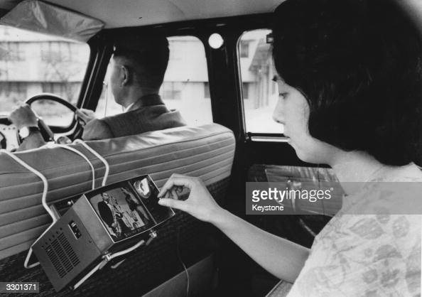 A woman uses a new portable micro television invented by the Japanese Sony Company in the back of a car