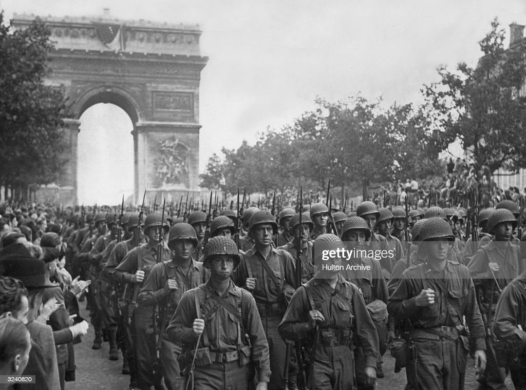 Rows of American troops parade through the Arc de Triomphe and down the Champs Elysees as crowds throng the sidewalks during the liberation of Paris. The troops were on their way to battle the retreating German Army.