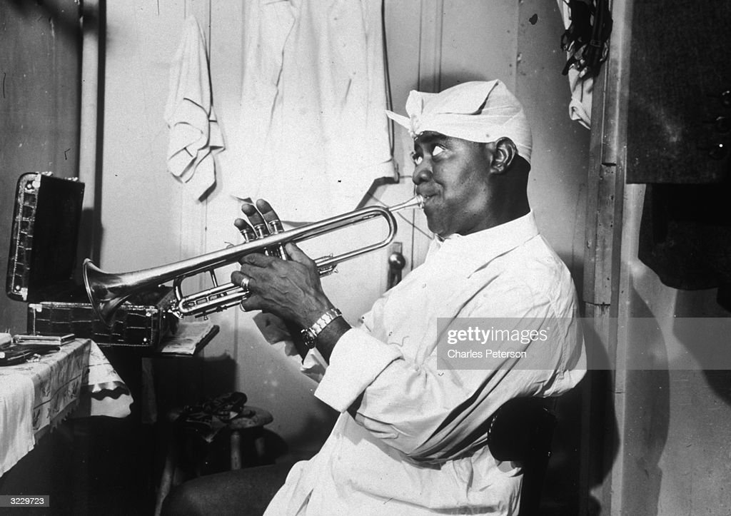 American jazz musician Louis Armstrong (1900 - 1971), wearing a white scarf on his head, practicing the trumpet in his dressing room at the Bop City nightclub where Armstrong's All Stars were headlining, New York City.