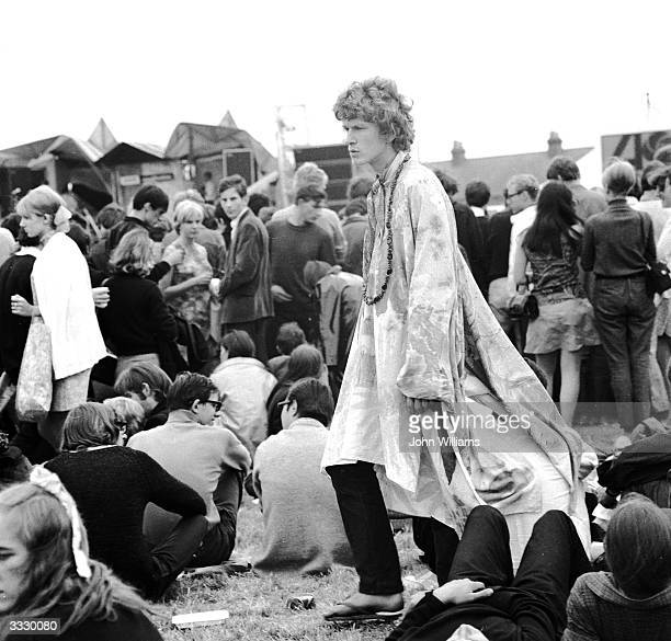 A young man walking through the crowd at a hippie festival in Windsor