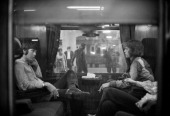 Paul McCartney of the Beatles and Mick Jagger of the Rolling Stones sit opposite each other on a train at Euston Station waiting for departure to...