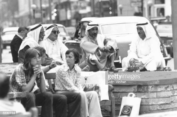 A group of Arabian men relaxing in a busy Kensington street London