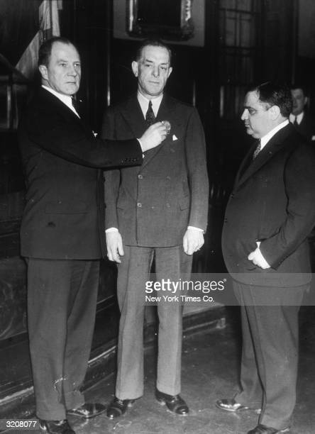 Commissioner Lewis J Valentine pins a first grade detective badge on William King who arrested Albert Fish while Mayor Fiorello LaGuardia watches...