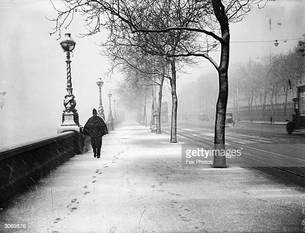 A lone policeman walks along the snow covered Embankment in London