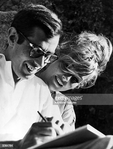 French film director Roger Vadim and his wife Annette drawing something amusing