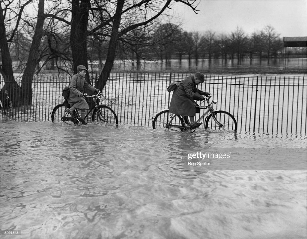 Two schoolboys struggle to cycle home along a flooded road where the River Mole, a tributary of the Thames, has burst its banks at Horsham in Surrey.