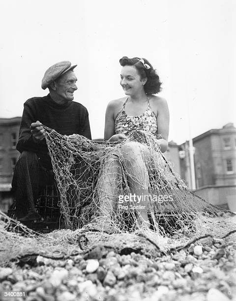53 year old fisherman Charlie Parsons gets some unexpected but welcome help mending his nets from friendly holiday maker Margaret Blenksby on...