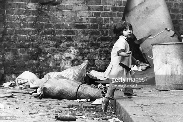 A very young child walking amongst the squalor of Brick Lane in the East End of London near Whitechapel