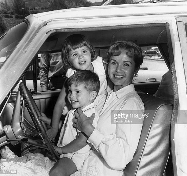 American actor Debbie Reynolds smiles while sitting in the front seat of an automobile with her children Todd and Carrie Fisher Hollywood California...