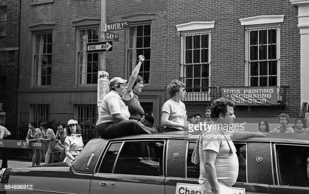 A Woman with her fist in the air showing solidarity sits through the sunroof of a Limousine as it travels down Waverly Place in Greenwich Village...