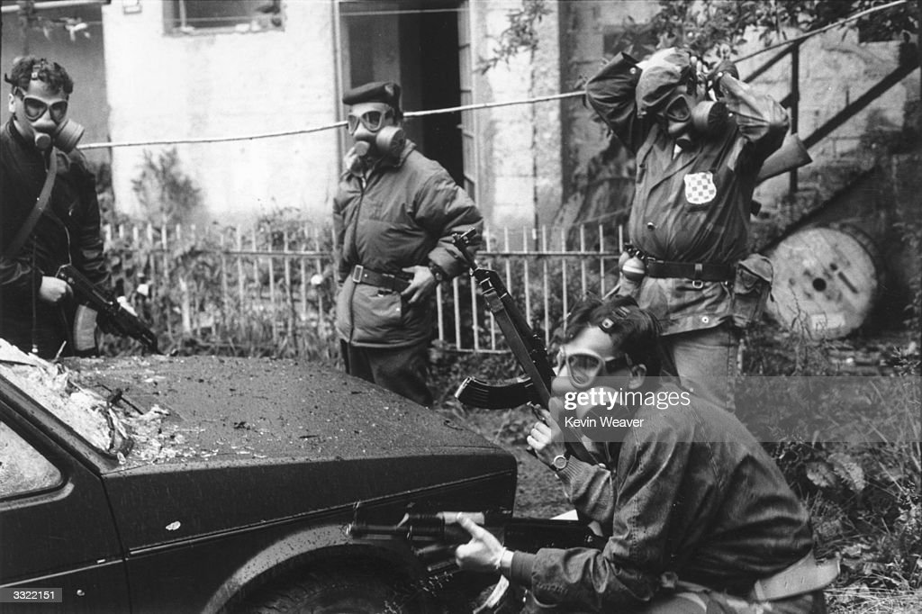 Gas masked soldiers of the Bosnian Army in action on the frontline at Dolniya Sarajevo during the war in Bosnia The soldier fixing his mask is in the...