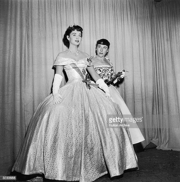 American costume designer Edith Head holds her Oscar as actor Marla English models the ball gown Head designed for Audrey Hepburn to wear in director...