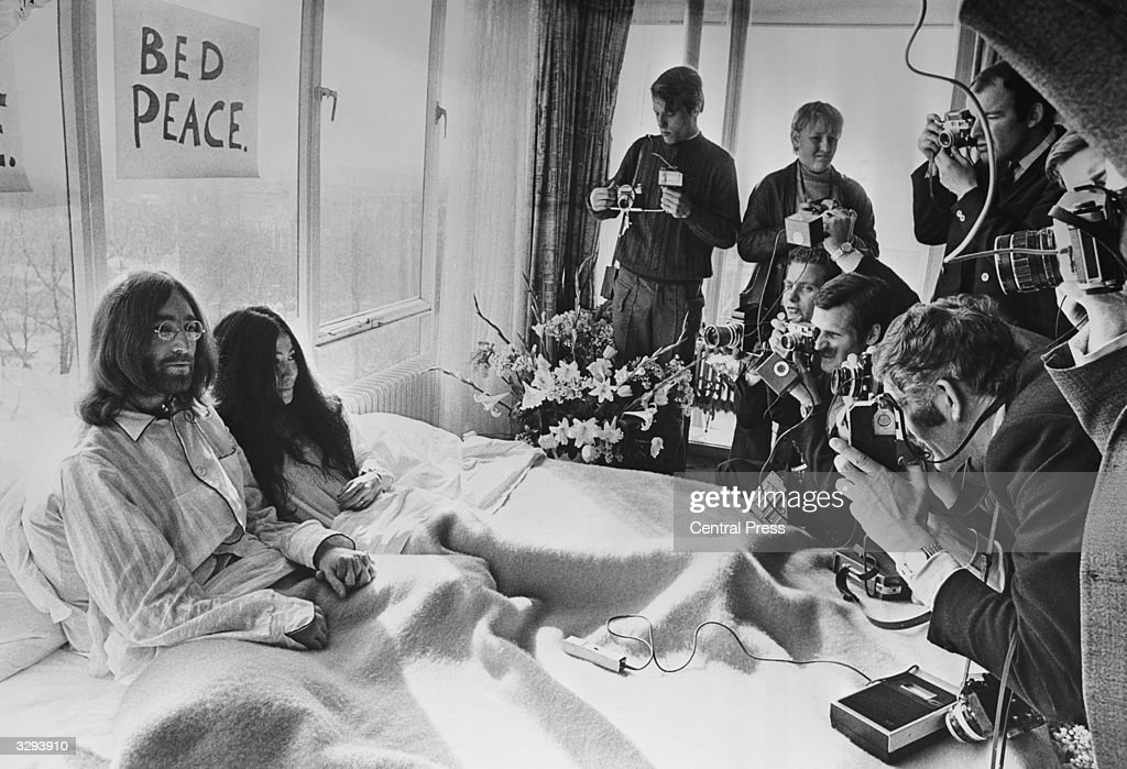 Beatles singer, songwriter and guitarist John Lennon and his wife of a week Yoko Ono receive the press at their bedside in the Presidential Suite of the Hilton Hotel, Amsterdam. The couple stayed in bed for seven days 'as a protest against war and violence in the world'.