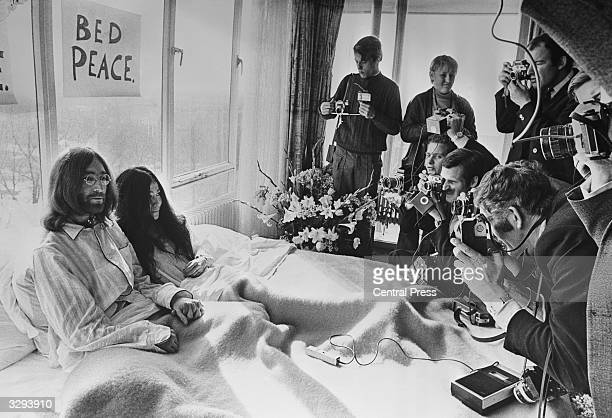 Beatles singer songwriter and guitarist John Lennon and his wife of a week Yoko Ono receive the press at their bedside in the Presidential Suite of...