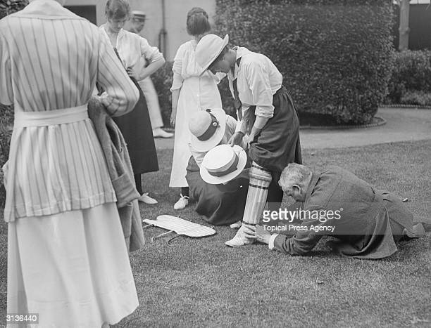 A cricketer has her pads fitted for Harrod's versus Woollands ladies cricket match