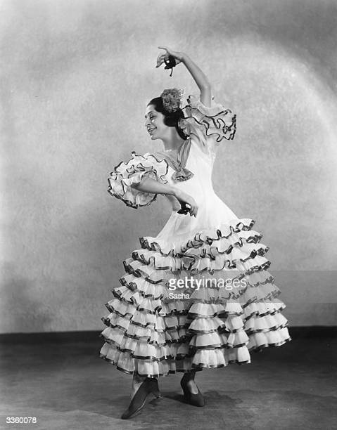 Argentinian dancer 'La Argentina' wearing an elaborate flamenco dress and striking a flamenco pose with a pair of castanets
