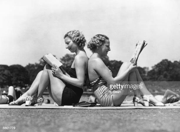 Two London women reading back to back as they sunbathe by the banks of the Serpentine in Hyde Park London