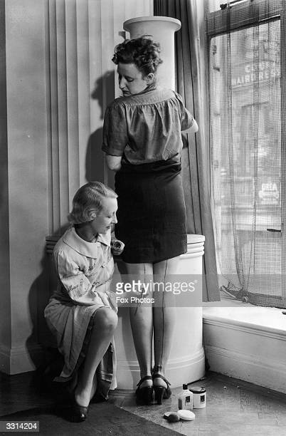 A representative of Max Factor paints cream stockings onto a woman's leg as a solution to the unavailability of stockings during the war