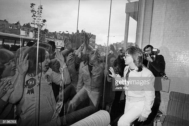 Hordes of screaming girls are separated from their idol David Cassidy by a pane of glass at the Thames television studio in London