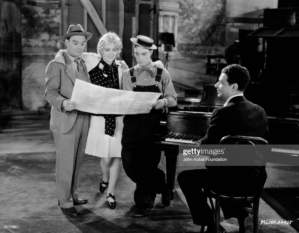 Anita Page and Buster Keaton (1895 - 1966) star in the early talkie musical 'Free And Easy' (aka 'Easy Go'), directed by Edward Sedgwick. Actor Cliff Edwards (1895 - 1971, left) joins them for a musical rehearsal.