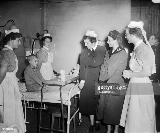 Queen Elizabeth II chats with young Patrick French during a visit to the London Hospital in Whitechapel Road