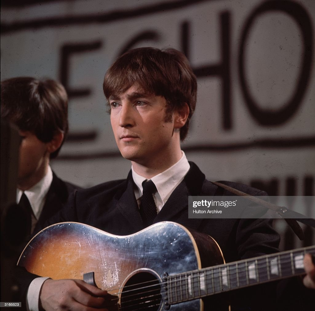 John Lennon (1940 - 1980), singer, guitarist and songwriter with the Beatles, plays an acoustic guitar during Granada TV's Late Scene Extra television show filmed in Manchester, England on November 25, 1963.