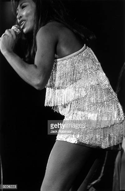 American rock singer Tina Turner leans forward on stage and sings into a handheld microphone during a concert by the Ike and Tina Revue at the Felt...