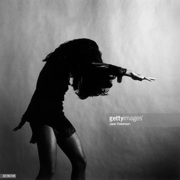American rock singer Tina Turner wearing a dark crocheted minidress dancing in profile with one arm stretched out in front of her while her long hair...