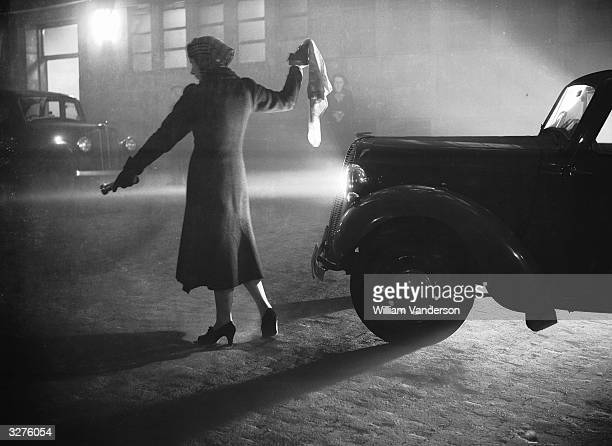 A woman leads a car through London's Regent's Park with a torch during the thick fog with visibility reduced to a few yards