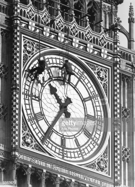 Two men abseiling down the front of St Stephen's or the Clock Tower at the Houses of Parliament London to clean the face of London's famous clock Big...