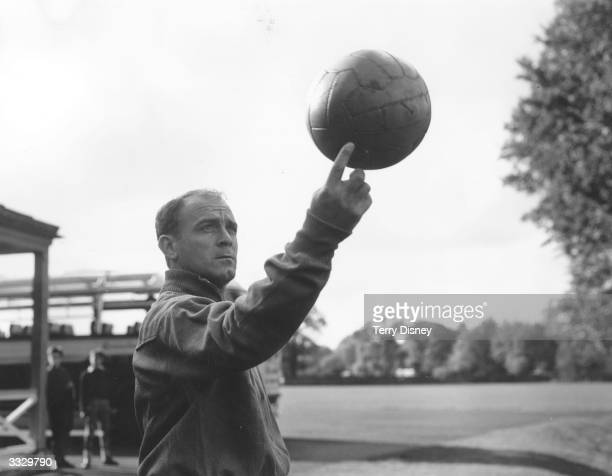 Spanish footballer Alfredo di Stefano one of the world's greatest forwards spinning a ball on one finger during Spain's team practice at Roehampton...