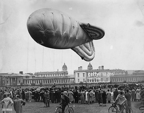 Crowds watching a balloon rising during a demonstration in Greenwich Park London of exercises carried out by the Auxiliary Air Force members of No...