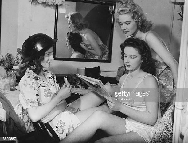 From left to right Huia Cooper Paddie Parsons and Pam Travers of Revudeville no138 relax in their dressing room at the Windmill Theatre London The...