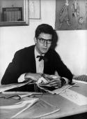 Yves SaintLaurent exwonder boy of Dior examining swatches of material in his office near the ChampsElysees where he is to open up his own fashion...