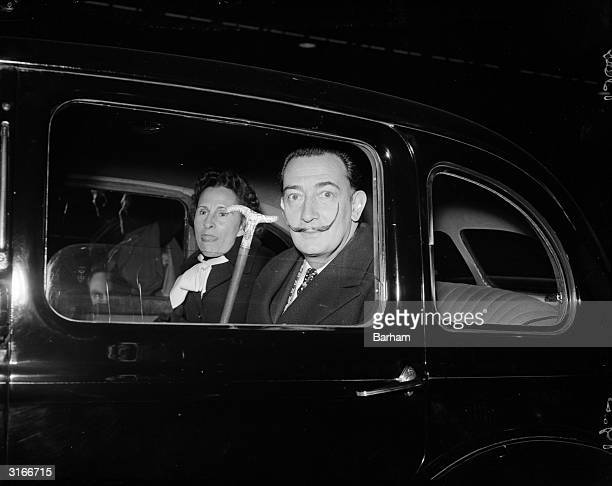 Salvador Dali and his wife Gala in a car while on a visit to London