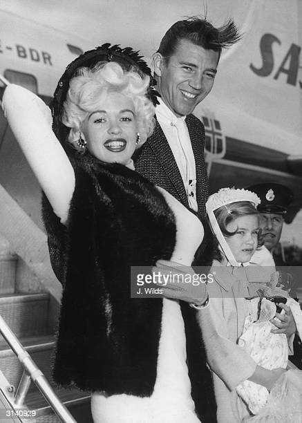 Hollywood sex symbol Jayne Mansfield arrives at London Airport with her husband Mickey Hargitay and her daughter Jayne Marie She is to costar with...