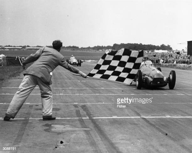 Giuseppe Farina receiving the chequered flag at an International Trophy Race at Silverstone