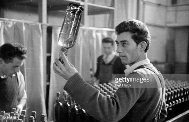A factory worker inspects a bottle of the liqueur manufactured by the monks at the monastery of the Grande Chartreuse in Dauphine southeastern France...