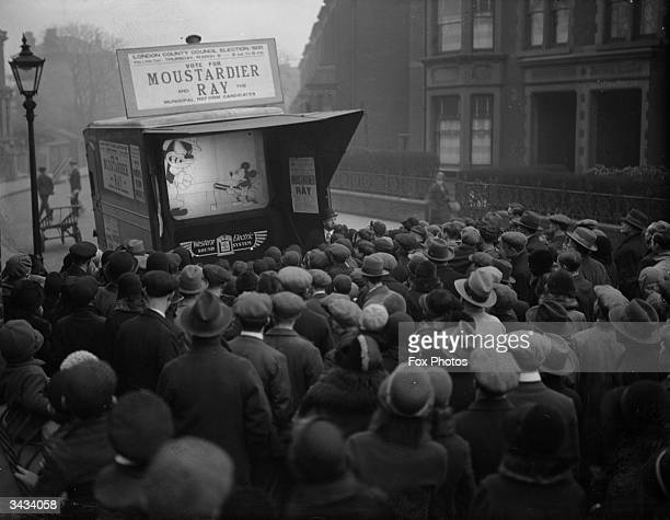 During an LCC election campaign run by Sir W Ray Mickey Mouse is showing on a small screen in a city streetThe sign above the screen says 'Vote for...