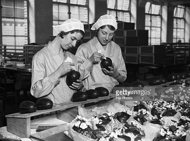 Two women at the Cadbury's chocolate factory in Bournville in the West Midlands join together chocolate Easter egg halves