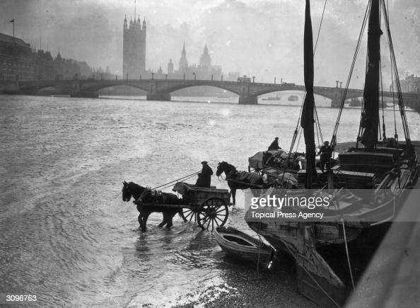 Horsedrawn carts are loaded from a barge at Lambeth south London