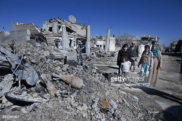A family from Kobani in Syria return home to find their home completely destroyed Unexploded large calibre mortar shells can be seen in the rubble