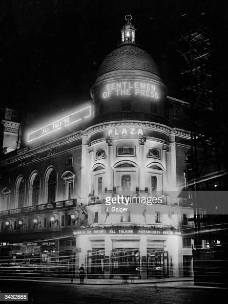 Neon signs for 'Gentlemen Of The Press' light up The Plaza cinema in London's Regent Street