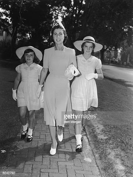 EXCLUSIVE Fulllength portrait of Jacqueline Bouvier her mother Mrs John V Bouvier III and her sister Lee walk along a brick sidewalk while attending...