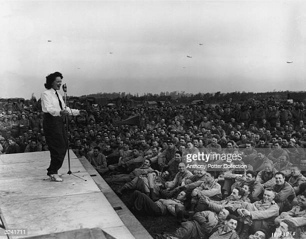 A woman wearing a necktie performs for soldiers at the first USO camp show France World War II