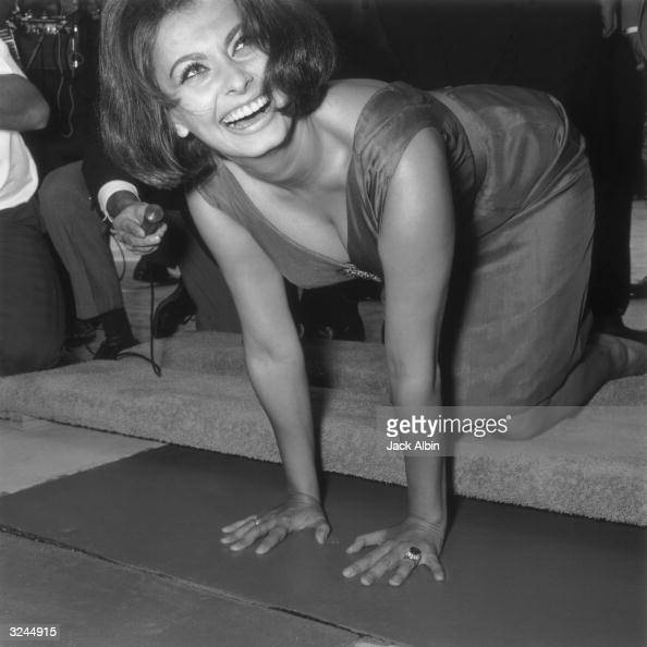 Italian actor Sophia Loren looks up and smiles while leaving imprints of her hands in wet cement at Grauman's Chinese Theater Hollywood California